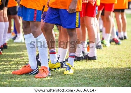 Young boys leg with football boots standing on football yard for football training.