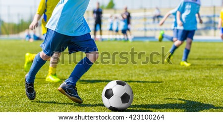 Young boys playing football soccer game. Running players in blue and yellow sports uniforms - stock photo
