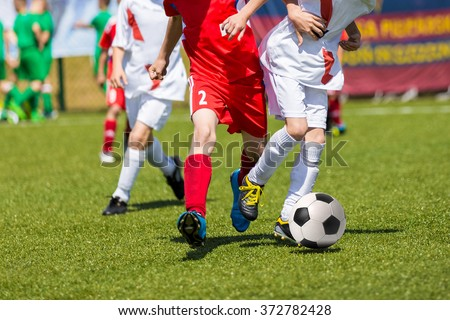 Young boys playing football soccer game. Running players in red and white uniforms - stock photo