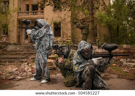 young boys playing paintball. boy holding a paintball gun. Boy in camouflage clothing. boy in a protective suit. Boy in a protective mask. game of war. war game. a team game. command.