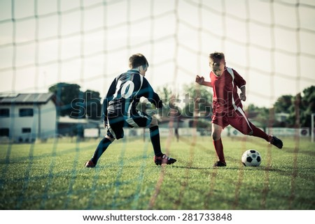 Young boys playing soccer - stock photo