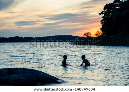 Young boys silhouette swimming and playing in a lake in Sweden after sunset - stock photo