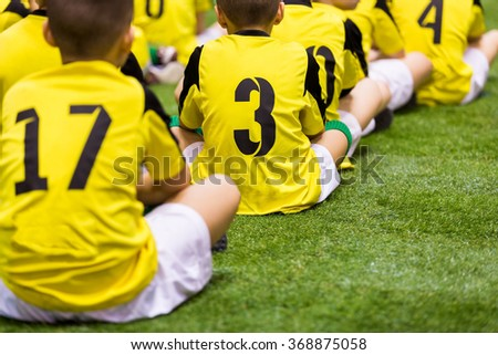 Young boys watching football match. Youth reserve players sitting on a soccer pitch ready to play football tournament. - stock photo