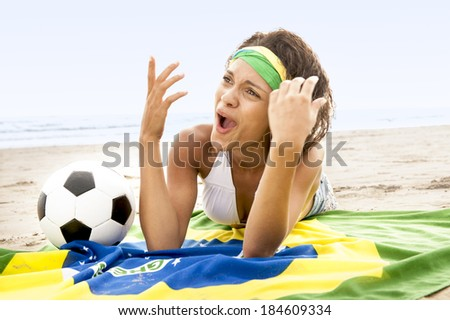 young Brazil supporter in team colors on beach making hand gestures - stock photo