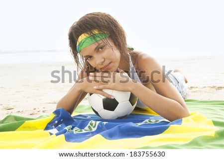 young Brazil supporter on beach with football and flag - stock photo