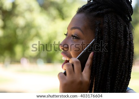Young Brazilian woman talking on the phone in the park