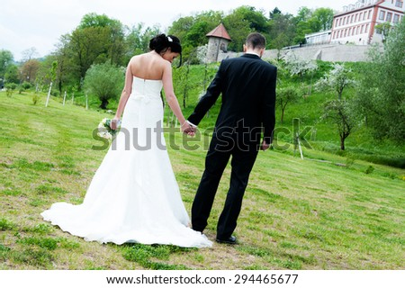 young bridal couple together in front of nature background