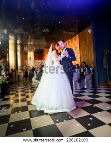 Young bride an groom dancing at restaurant - stock photo