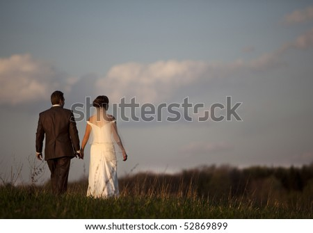 young bride and groom against blue sky with clouds - stock photo