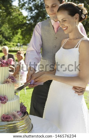 Young bride and groom cutting wedding cake in garden