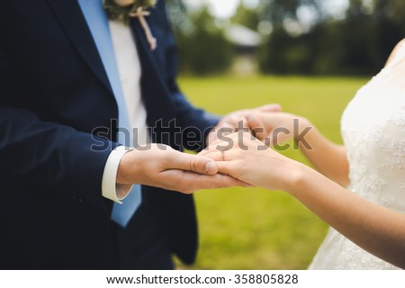 young bride and groom hand gently touch each other close-up before the wedding ceremony
