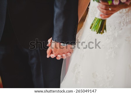 Young bride and groom holding hands outdoors