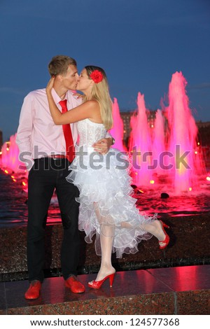 Young bride and groom kiss near pink fountains. Pink wedding. - stock photo