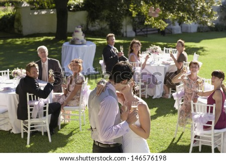 Young bride and groom kissing while wedding guests toasting champagne flutes in garden - stock photo