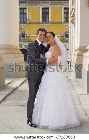Young bride and groom posing for the camera in front of large columns