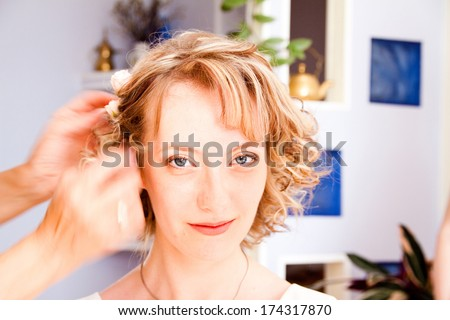 Young bride applying wedding hairstyle by hairstyle artist - stock photo