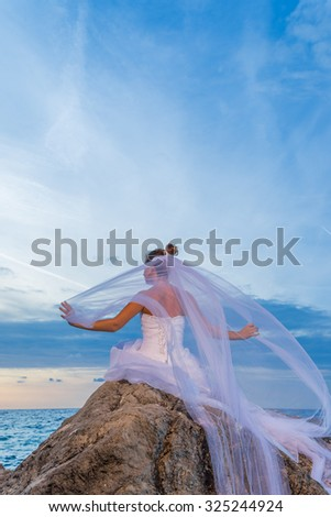 YOung bride by the sea at sunset in Greece - stock photo