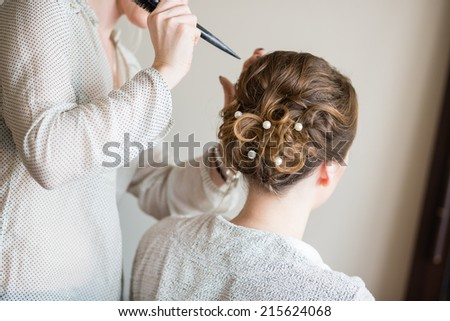 Young bride getting her hair done before wedding - stock photo
