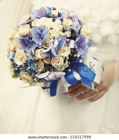 young bride holding a wedding bouquet - stock photo