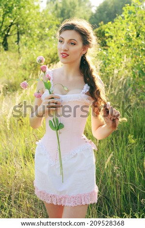 Young bride in a pink corset outdoors admiring flowers