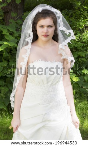 young bride in a white wedding dress standing in a park