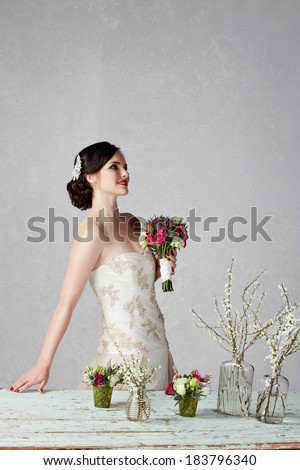 young bride in beige embroidered wedding dress at grunge table with fresh flowers on studio background with space for text