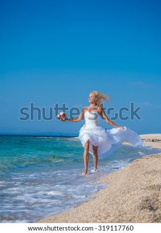 Young bride in wedding drees having fun on the beach in Greece