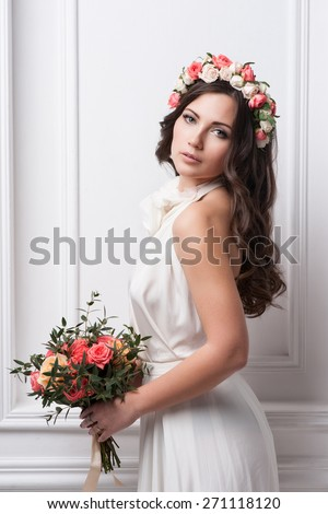Young bride in wedding dress holding bouquet, studio shot  - stock photo