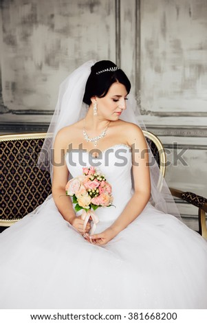 Young bride is sitting in an armchair. Beautiful Bride Portrait wedding makeup, wedding hairstyle, Wedding dress. Wedding decoration. soft selective focus. gorgeous young bride at interior