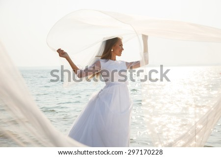 Young bride is standing near sparkling water with long flying veil.Selective focus