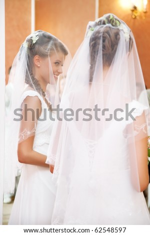 Young bride looking at the mirror. - stock photo