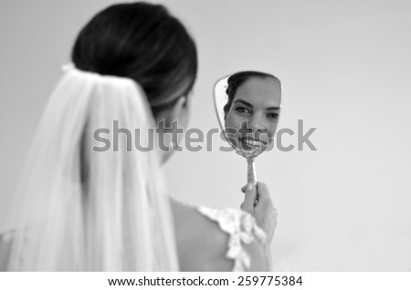 Young bride looks at herself in the mirror on her Wedding Day. Woman,self esteem, self image, wedding and marriage concept. copy space - stock photo