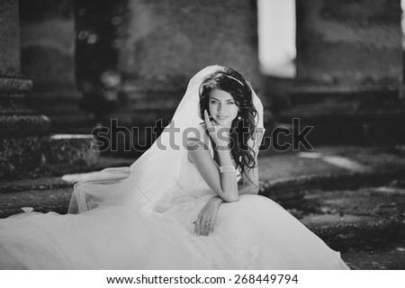 Young bride  posing  against an old church. Wedding picture in black and white.  - stock photo