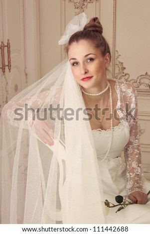 Young bride sitting on a chair with a white rose in her hand - stock photo