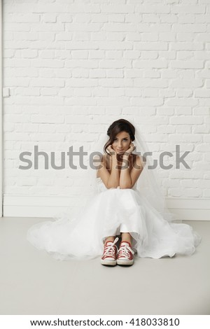 Young bride sitting on floor in red sneakers and wedding dress, looking at camera. - stock photo