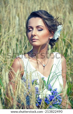 young bride wearing a white wedding dress sitting in the grass - stock photo