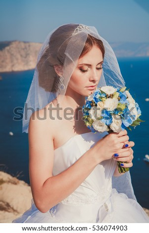 young bride with a veil and a white dress standing on blue sea background