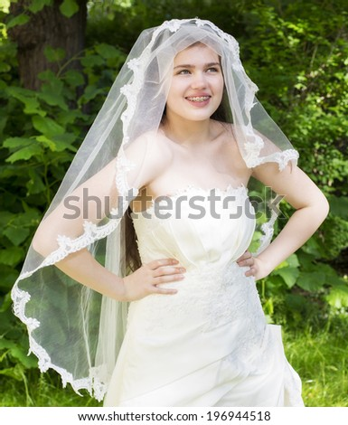 young bride with braces in a white wedding dress standing in a park - stock photo