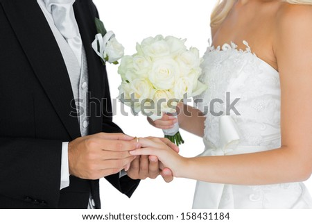 Young bridegroom putting on the wedding ring on his wife's finger on white background - stock photo