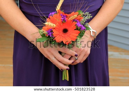 Young bridesmaid in purple gown, holding colorful Fall bouquet wrapped in burlap, ready to help celebrate the bride's wedding day.