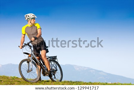 Young bright man on mountain bike