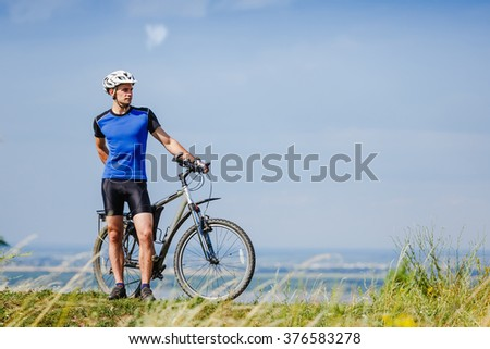 Young bright man on mountain bike - stock photo