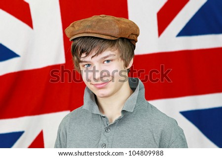 Young British boy with hat in front of Union Jack national flag