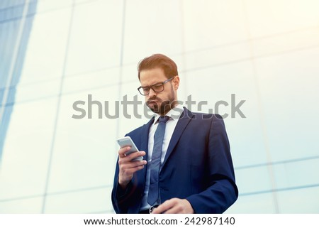 Young broker receiving bad news from exchange speaking on phone outside the office - stock photo