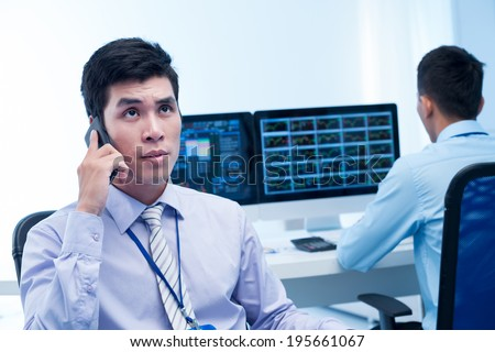 Young broker talking on the phone while his colleague is analyzing market