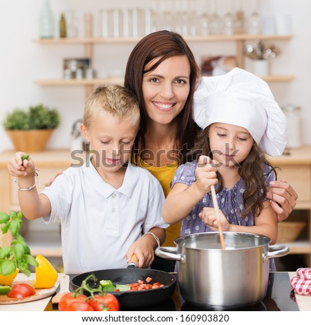 Young brother and sister learning to cook standing with their mother in the kitchen preparing spaghetti, the little girl is wearing a chefs toque - stock photo