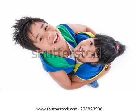Young brother and sister looking into camera, top view, - stock photo