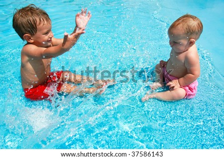 young brother and sister playing with water in pool