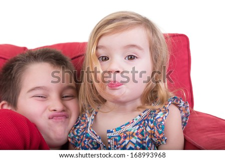 Young brother and sister pulling funny faces holding their breath and screwing up their noses as they sit together playing on a red couch