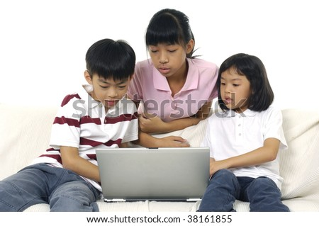 Young brother and sister sitting on couch at home, browsing internet on laptop computer - stock photo